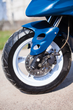 Front wheel of blue modern scooter on the gravel road. Foto de archivo