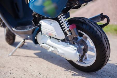 Rear wheel of blue modern scooter on the gravel road. Foto de archivo