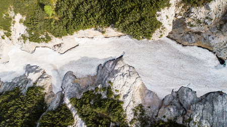 Aerial view of the mudflow with snow high in the Alpine mountains, Top view