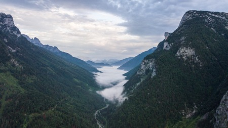 Aerial view of the morning foggy landscape in the alpine mountains.