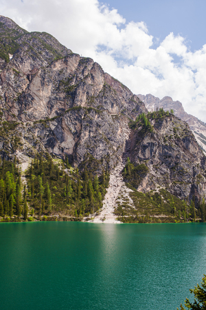 Mudflow with snow high in the Alpine mountains lake, Lago Di Braies.