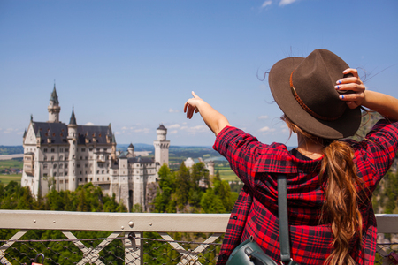 The girl in the hat shows by hand on Castle of Neuschwanstein in Alpine mountain.
