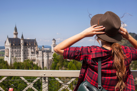 The girl in the hat looks Castle of Neuschwanstein in Alpine mountains.