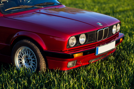 The front of the old, red, German car that stands on the grass. Stok Fotoğraf
