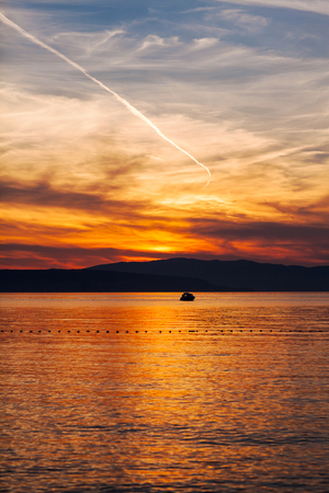 Orange sunset on the sea with the sun, a beautiful sky on the background of mountains.