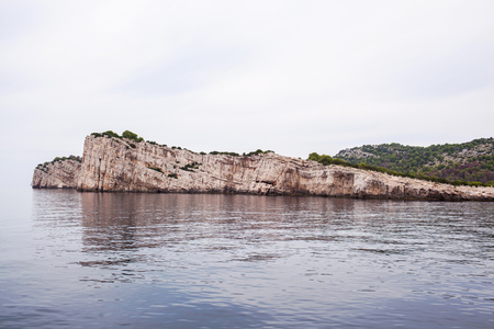 A large stone wall of beige stone in the sea.