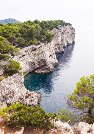 A large stone wall of beige stone in the sea with forest. Stock Photo