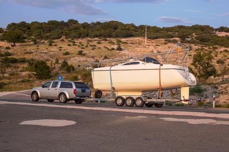 Car pulls yacht on trailer. Stock Photo