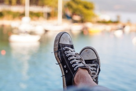 Old black sneakers on the background of the sea with yachts.