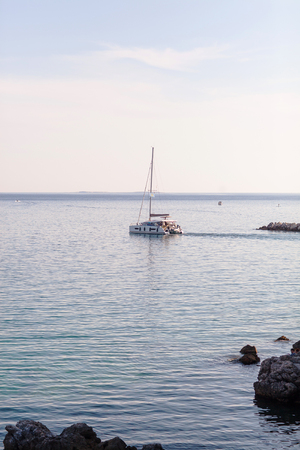 Sailing yacht sailing from shore. Stock Photo