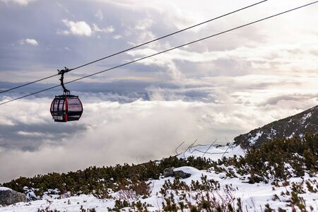 Cableway cabin above the clouds at sunset. Banco de Imagens