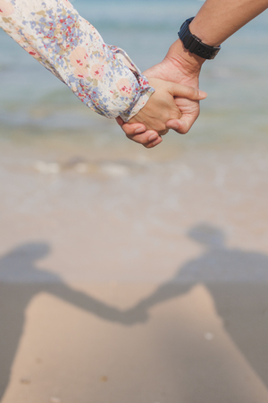 relationship love: Holding hands couple on beach with shadow. Romantic love and happiness concept image with happy young couple. Closeup.