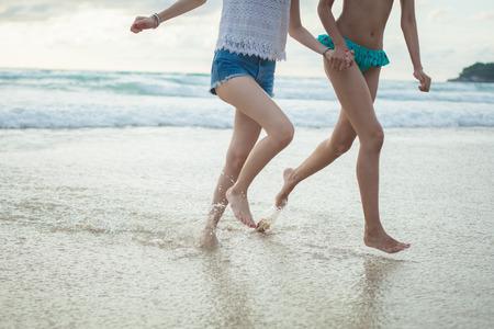Dos niñas corriendo en la playa bajo la ira vista