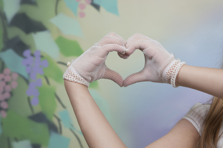 detail of gloved hands of a communion girl marking the heart shape 스톡 콘텐츠