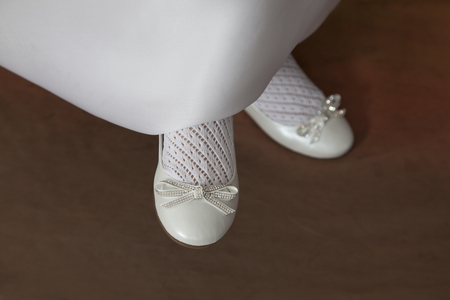 detail of the shoes with a bow worn by a girl dressed in white of the first communion Standard-Bild - 98975022