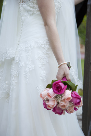 detail of the bridal bouquet in salmon and pink colors, which holds the bride placed on her back, wearing her white dress