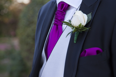 detail of a suit of groom with a white rose in the lapel of the blue suit with gray vest and tie and purple handkerchief