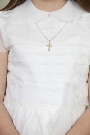 detail of communion hands of a girl dressed in white,wearing a gold chain with a cross Stock Photo