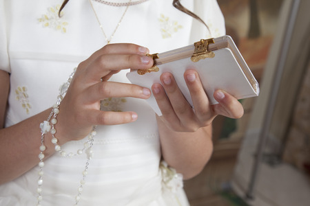 detail of the hands of communion girl dressed in white and holding a book and a bracelet on her wrist Stock Photo
