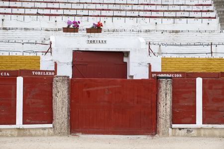 Detail of the interior of a bullring where you can see the number of seats, the sand, the door where bulls leave the square, the corridor where the bullfighters are. Stock Photo