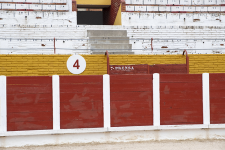 Detail of the interior of a bullring where you can see the number of seats, the sand, the door where bulls leave the square, the corridor where the bullfighters are. Stock Photo - 106023254