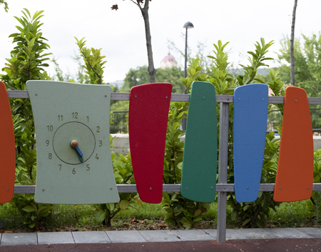 detail of a playground where you can see a clock with numbers and handles Stock Photo