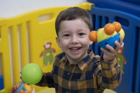 two years old boy playing in a park of red, blue, green, yellow, orange balls. dressed in a yellow and blue plaid shirt