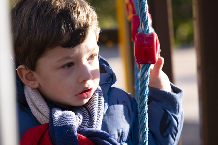 two year old boy playing in an outdoor park on a sunny winter day,dressed in a blue coat and brown trousers Stock Photo