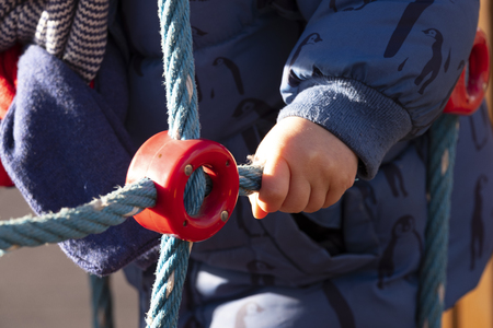 Detail of the hand of a two year old boy playing in an outdoor park on a sunny winter day,dressed in a blue coat and brown trousers