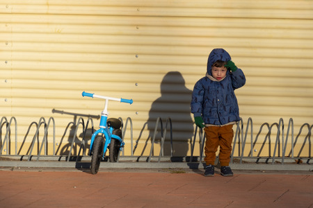 Two years old boy parking his blue bicycle without pedals in a bike park, on a cold and sunny day in the late fall early winter. he is dressed in a blue hooded coat, brown pants, green gloves and scarf
