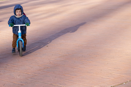 two year old boy riding a blue bike without pedals on a cold but sunny winter day where you can see his shadow projected on the ground.The boy is dressed in a blue coat with a hood and brown trousers with green gloves in his hands