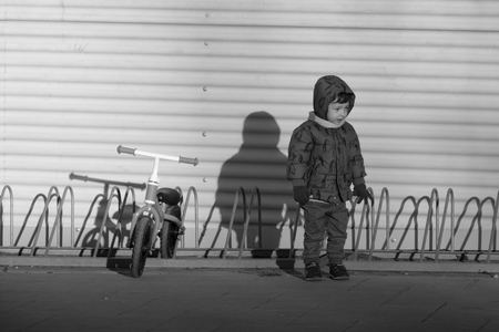Black and white image of a two years old boy parking his blue bicycle without pedals in a bike park, on a cold and sunny day in the late fall early winter. he is dressed in a blue hooded coat, brown pants, green gloves and scarf