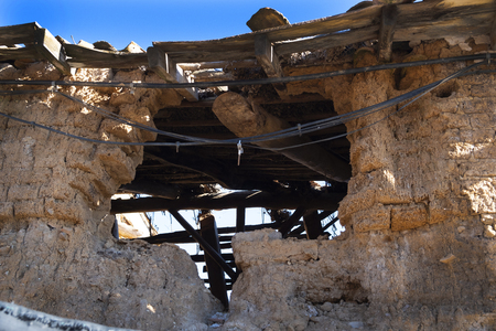 ruins of an old village house made of adobe bricks (mixture of straw and stone mud),where you can see the old wooden beams, the old light cables hanging next to the new cables.