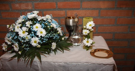detail of the table of the offering on the day of the first communion of a group of boys and girls. where you can see, a center of white and blue flowers, the quality of wine, a candle adorned with white daisies that symbolizes light, the body of Christ in the form of bread, and a jug of water that symbolizes purity.