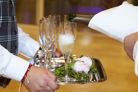 detail of the hands of a waitress holding a tray with four glasses, while another waiter serves with a bottle of champagne, the glasses, filling them with a bubbling yellow liquid.