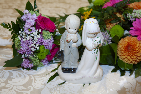 detail of the bridal dolls, next to the bouquet of flowers of the bride in green, purple and pink colors