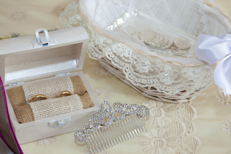 still life on the double bed of the accessories of a bride with arras, a wooden box with the wedding rings and a hair ornament Stockfoto