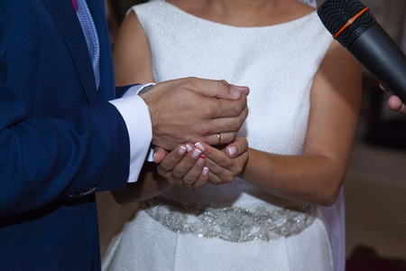 detail of the hands of the bride and groom just at the moment in which the bride gives the arras as a symbol of the goods that are going to share the groom wearing a suit of blue