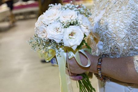 detail of a bouquet of flowers in light colors, between gold and whites with a golden colored bow. The bride holds it with both hands and on her left wrist wears a bracelet of brown balls