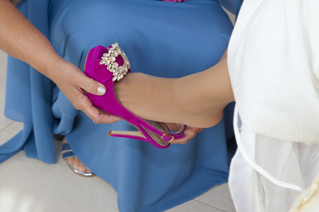 detail of the shoes of a bride on her wedding day,where the godmother in blue dress helps the bride to put on her pretty and original pink shoes with diamonds Stock Photo