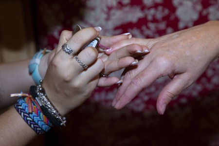 close up of the hands of a teenage girl who is painting her nails to a woman
