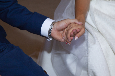 detail of the hands of the couple during the church ceremony where you can see that the groom is wearing a blue suits and the bride a nice white dress with painted nails