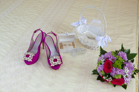 Still life on the double bed of the accessories of a bride on her wedding day, pink shoes with bright decorations, a wicker basket with the arras, a wooden box with the wedding rings, the bouquet of flowers and an ornament for hair. Stock Photo
