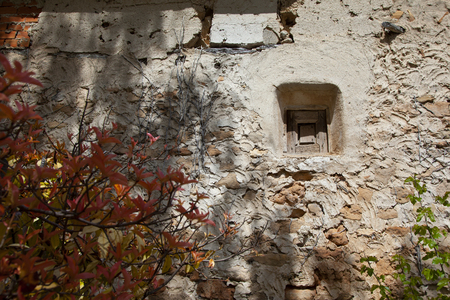wall of an old town house made of stones, brick, cement, plaster. With areas better preserved than others. The window is very small and wooden os they were before.