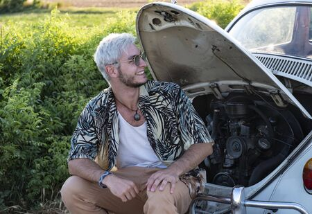 caucasian boy with a beard and blond-haired hair and sunglasses. Smile sitting in the back os a your car. Where you can see the engine of the broken down car.