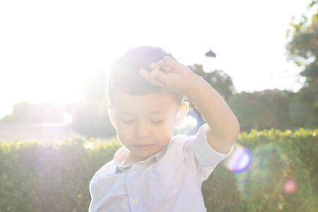 two year old boy enjoying a sunny day. The light enters the objective of the camera creating a magical light
