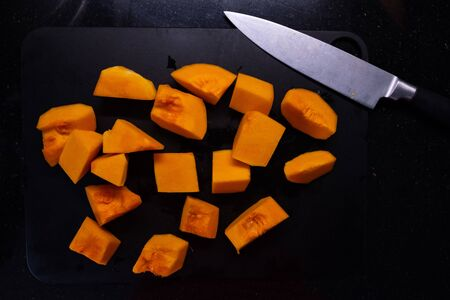 on the table of a cook you can see pieces of pumpkin, orion and his knife Stock Photo