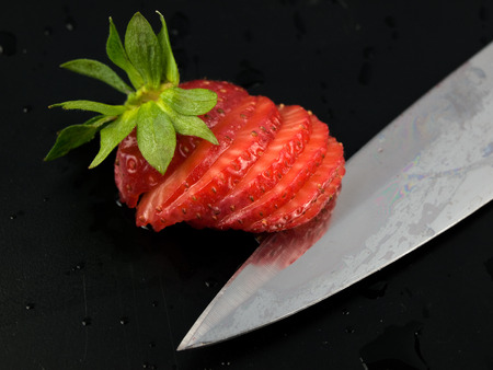 srawberry: sliced srawberry with kife on black