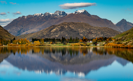 Reflections of autumn trees and mountains in Lake Hayes, Queenstown 写真素材