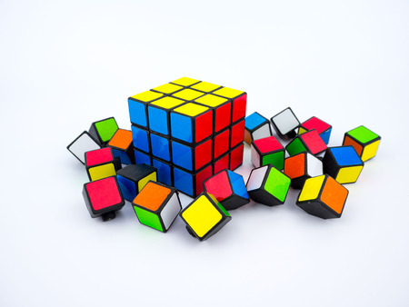 invented: Bangkok, Thailand - October 27th, 2016: Colorful Rubiks cube and broken cube pieces on white background Editorial